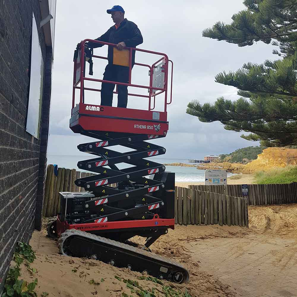 Athena bi-levelling tracked scissor lift working on sloping soft sand