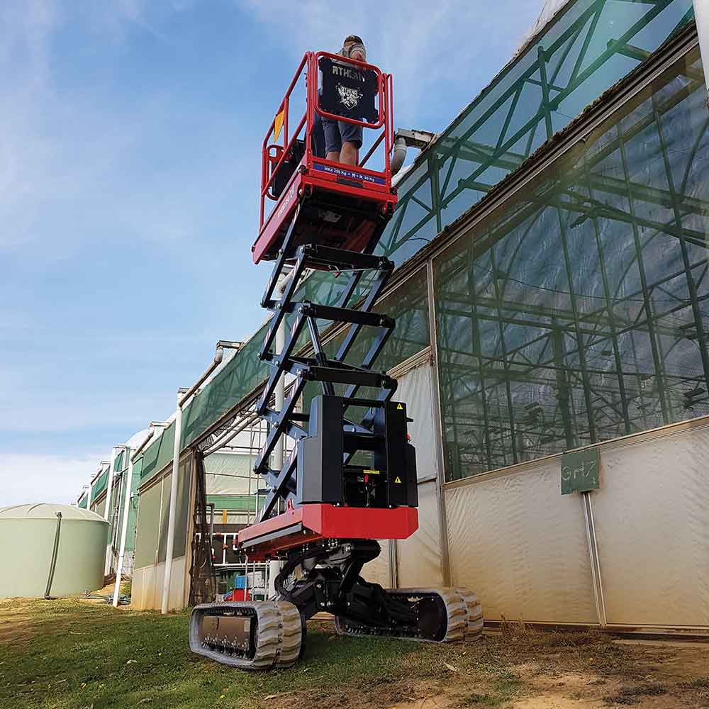 Athena bi-levelling tracked scissor lift working on sloping grass