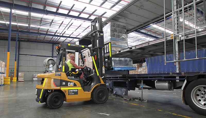 Bluestar operator unloading truck with United's CAT forklift